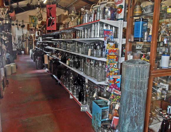 new old shelving holding antique and vintage glass bottles at heaths antiques bangalow
